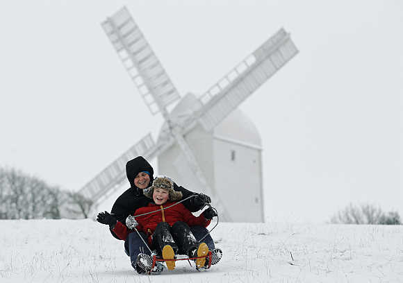 Eight-year-old Carl Attwater and his mother Jane ride a sled downhill in front of the Jill Windmill at Hassocks in England.
