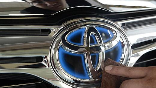 A worker cleans the logo of a Toyota car at dealership store.