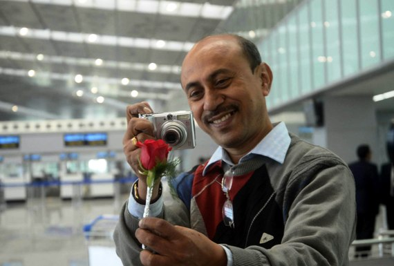 A passenger takes photograph of the rose that he got as a welcome gift at the new Kolkata airport.