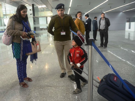 A mother and a child engage in a conversation as a security guard looks on at the new Kolkata airport.