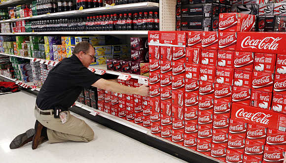 An employee arranges cartons of Coca-Cola at a store in Alexandria, Virginia, United States.