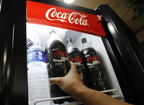 A man takes a bottle of Coke Zero out of a fridge at a supermarket in Caracas, Venezuela.