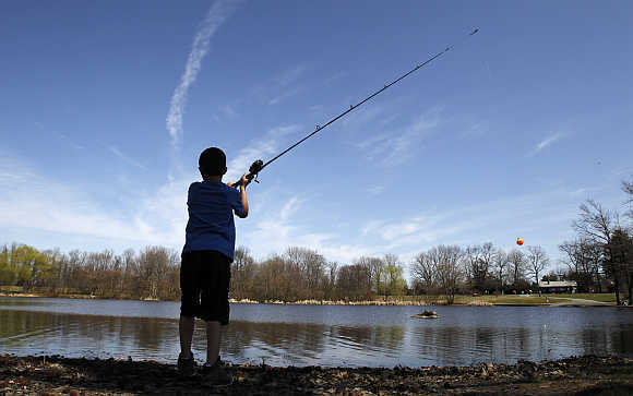 Zach Andrews casts a fishing line into a pond at Bellevue State Park near Wilmington, Delaware.