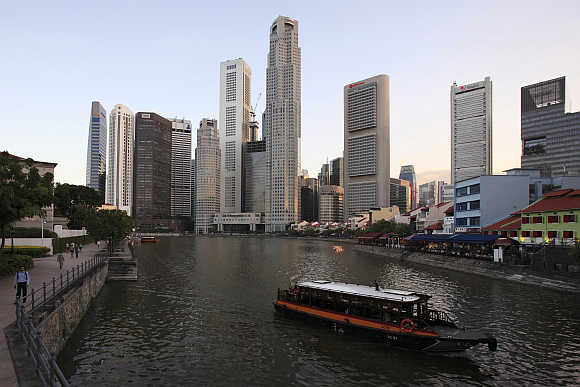 A tour boat travels up Singapore River past the skyscrapers of the financial district.