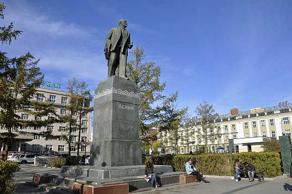 Locals sit near a statue of the founder of the Soviet state Vladimir Lenin in Ulan Bator.