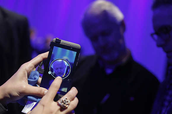A man uses an Apple iPhone to photograph new BlackBerry devices during the Blackberry 10 launch in New York.