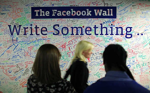 People walk past the Facebook wall inside the Facebook office in New York.