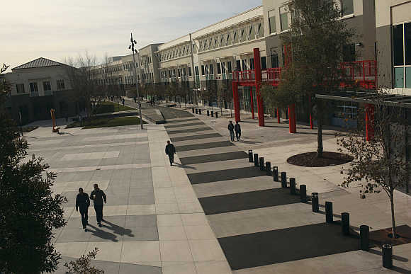 Employees walk along a walking and bicycle path at Facebook headquarters in Menlo Park, California.