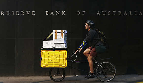 A worker on his bike rides past the Reserve Bank of Australia building in central Sydney.