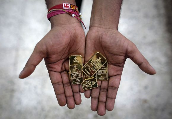 An employee poses with gold biscuits inside a jewellery showroom in Mumbai.