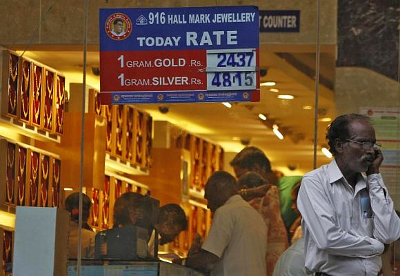 A man speaks over his mobile phone as customers buy gold at a jewellery showroom in the southern Indian city of Chennai.