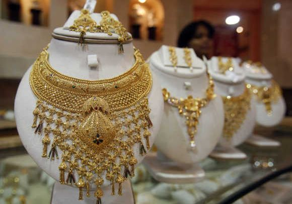 A saleswoman stands behind the showcased gold necklaces at a jewellery showroom in Agartala.