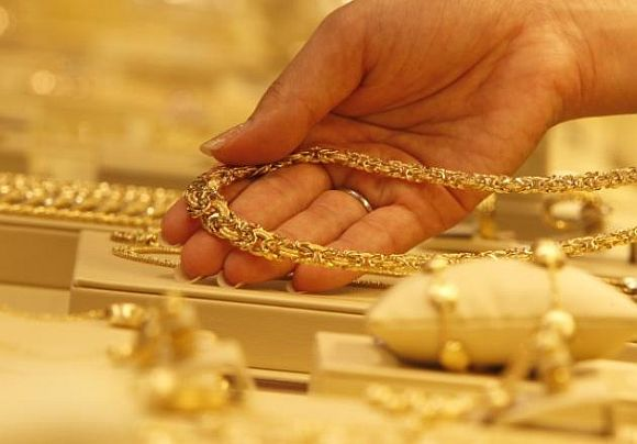 An employee displays a gold necklace.