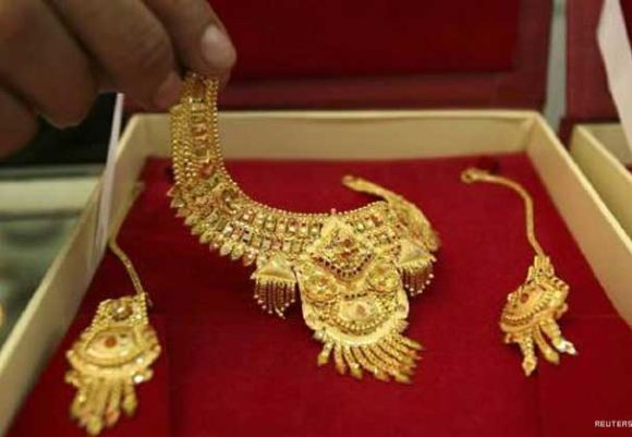 A shopkeeper displays gold jewellery at a shop in Jammu.