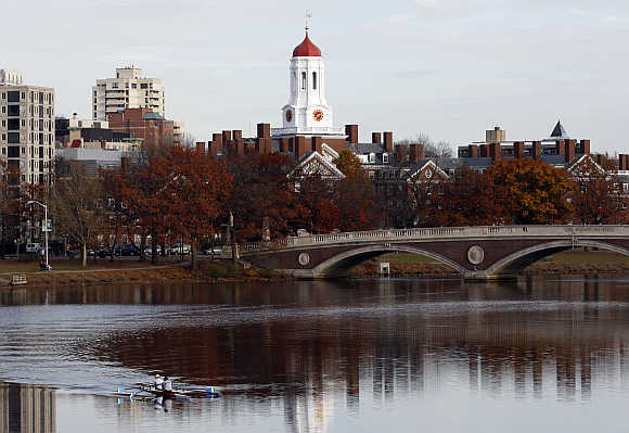 A pair of rowers are seen in the Charles River as Harvard University is reflected in the water in Cambridge, Massachusetts.