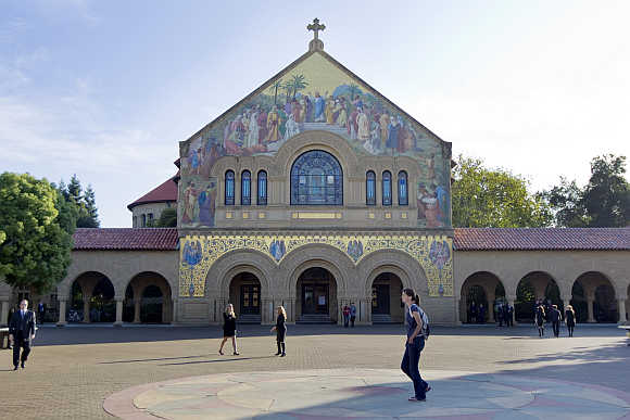 People walk in front of a church on the campus of Stanford University in Palo Alto, California.