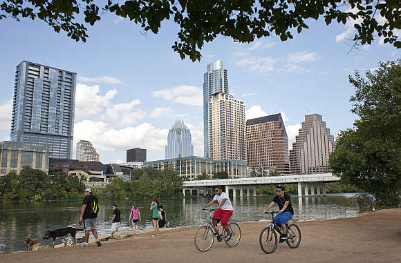 Cyclists pass beneath the downtown skyline on the hike and bike trail on Lady Bird Lake in Austin, Texas, United States.