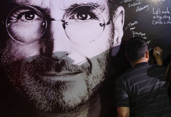 A man signs his name on a sympathy board set up for 'Steve Jobs Day' in Manila.