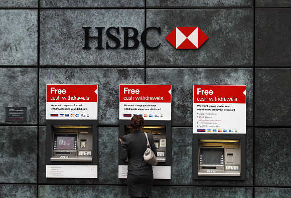 A woman uses a cash point machine at a HSBC bank in the City of London.