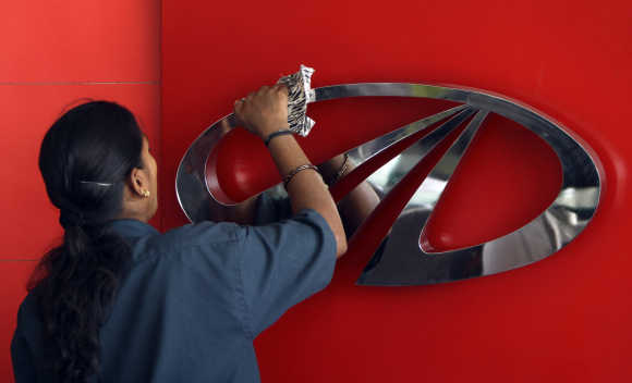 A worker cleans a logo of Mahindra & Mahindra.