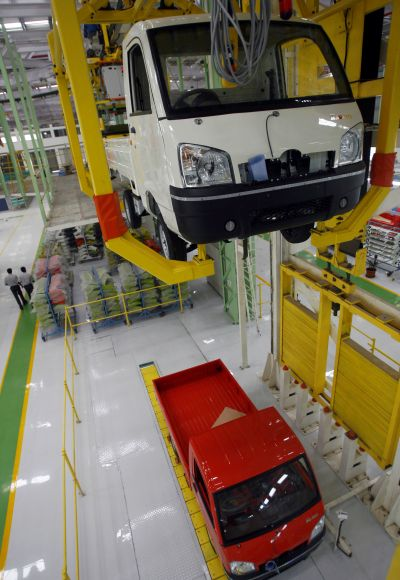 Employees walks past an assembly line of Maxximo, a light commercial vehicle, at a new plant of Mahindra and Mahindra in Chakan.
