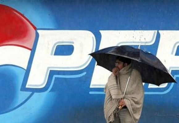 A man stands next to a Pepsi advertisement while using an umbrella in the rain