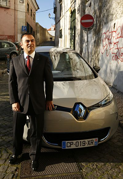Carlos Ghosn, chairman and chief executive cfficer of Renault, poses next to a Renault Zoe.