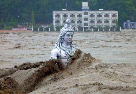 A submerged statue of the Hindu Lord Shiva stands amid the flooded waters of river Ganges at Rishikesh.