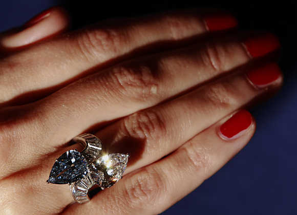 A Bonhams employee poses with the Bvlgari crossover ring set with 3.72 carat fancy vivid blue diamond and 3.93 carat diamond at Bonhams auction house in London.