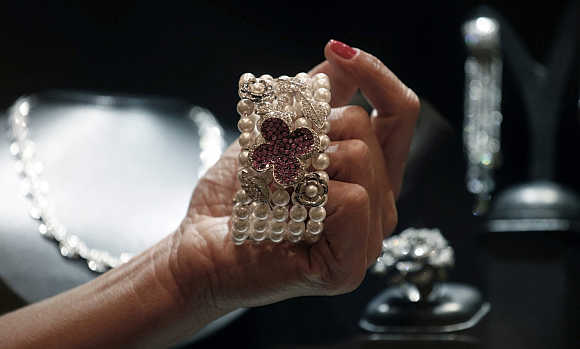 A shop assistant shows a bracelet from Brazilian designer Mauricio Monteiro, containing a selection of large pink sapphires, pearls and diamonds, at the Iguatemi mall in Sao Paulo, Brazil.