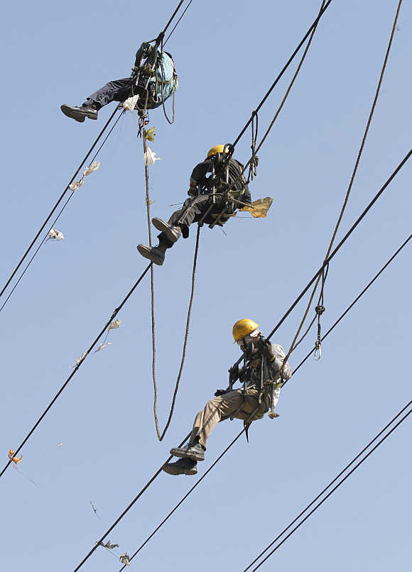 Labourers remove kites tangled up in electric power cables in Ahmedabad.