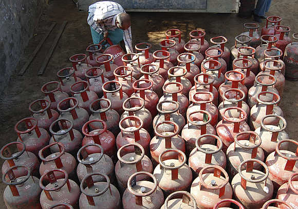 A vendor loads empty Liquefied Petroleum Gas cylinders in Mathura.