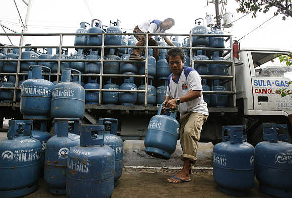 Workers deliver liquid petroleum gas cylinders in Manila, the Philippines.
