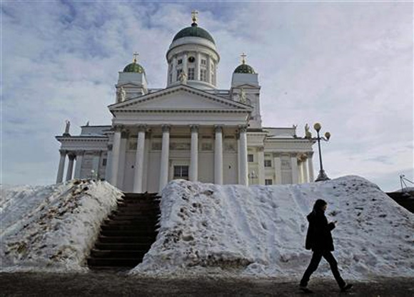 A woman walks past Helsinki cathedral.