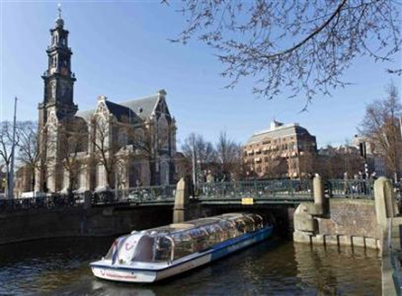 A tourist boat passes under a bridge next to the Westerkerk church in Amsterdam.