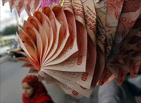 A Kashmiri woman walks under a garland made of rupee notes on display at a market in Srinagar.