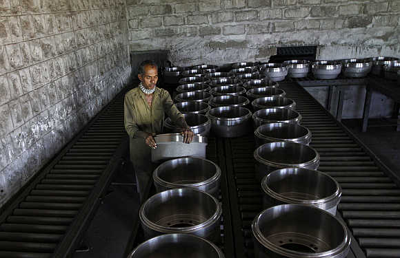 A worker arranges brake drums used in truck wheels at a steel factory in the outskirts of Coimbatore.