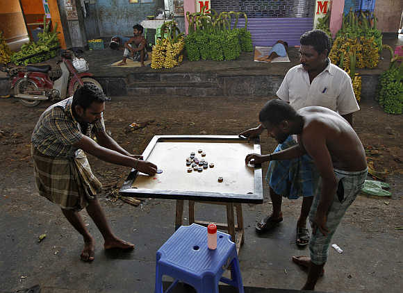 Workers play carom at a wholesale fruit market in Coimbatore.