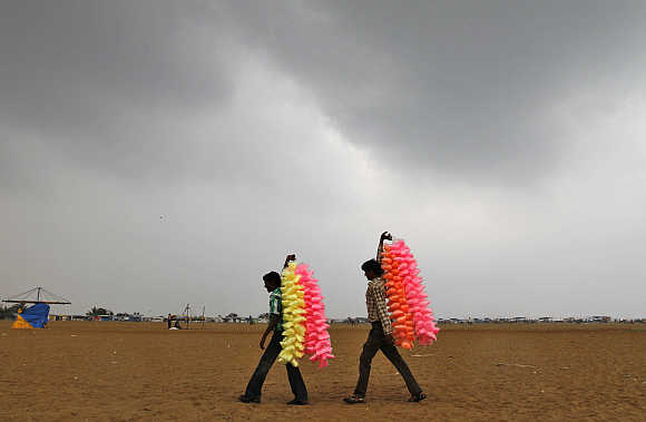 Vendors carry sugar candies for sale at Marina beach in Chennai.