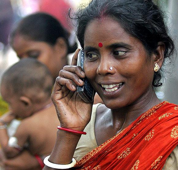 Tulsi Prasad, an Indian slum dweller, uses a mobile phone.