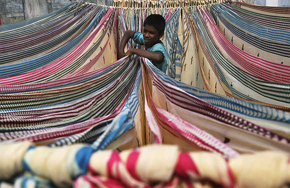A boy separates starched sarees left to dry on the roof of a cotton factory in Hyderabad.