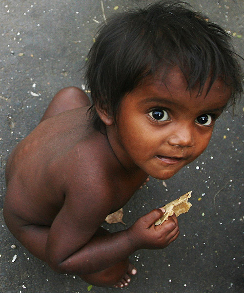 A boy eats roti at a slum in Mumbai.