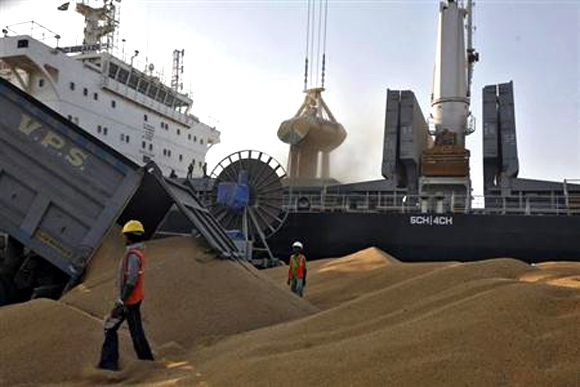 A dumper unloads wheat as a crane loads onto a cargo ship at the Mundra port in Gujarat.