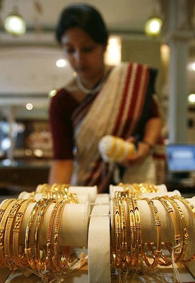 A woman looks at gold jewellery on display at a jewellery showroom.