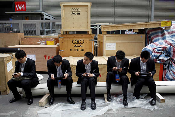 Men sit next to boxes of German carmaker Audi in Shanghai, China.