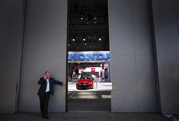 A man uses a mobile phone while standing outside a Honda display in New York.