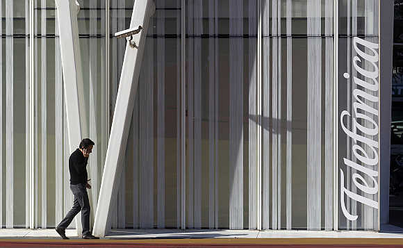A man speaks on a mobile next to Telefonica's tower in Barcelona, Spain.
