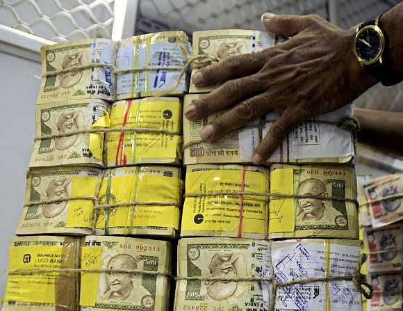A bank employee counts bundles of rupee notes at a cash counter in Agartala, Tripura.