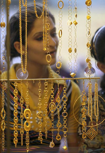 A woman looks at gold jewellery.