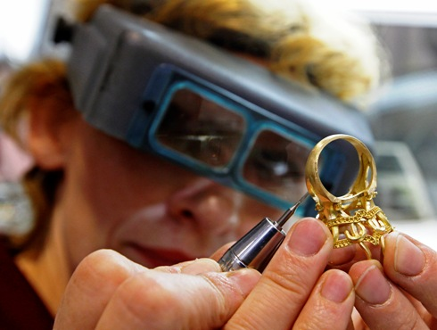 A jeweller works on a golden ring at a factory.